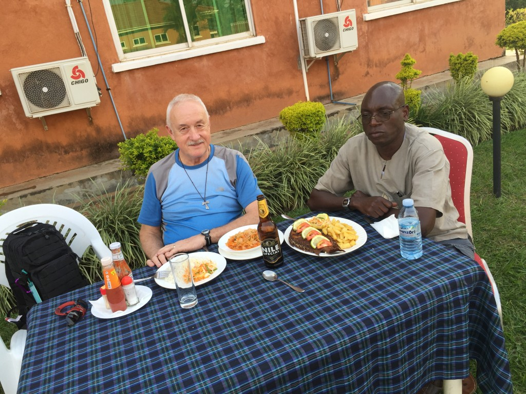 An exhausted Deacon and friend Bob Okello sharing a snack at Churchill downs in Gulu.
