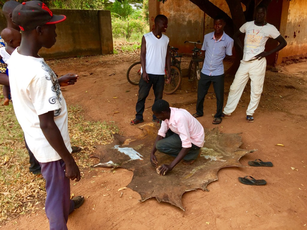 The actors putting the final touches on an animal hide used to sit on.