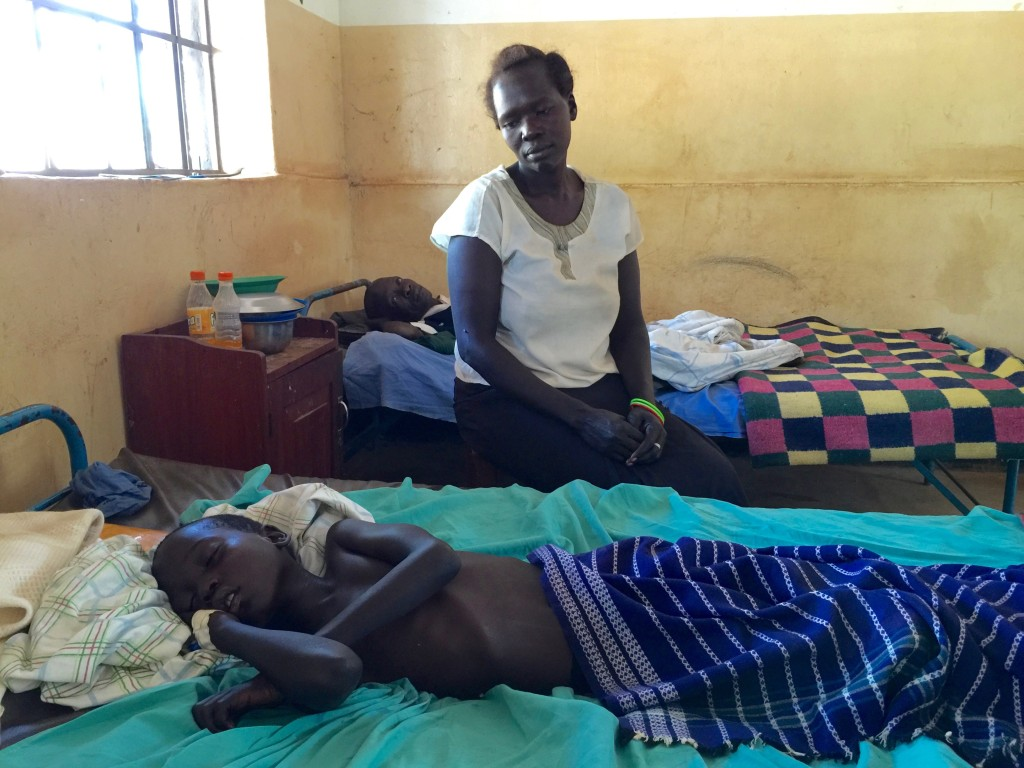 The mother sits near her son who is extremely sick with malaria.